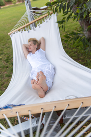 beautiful young woman enjoying free time while resting on white hammock in the backyard Imagens