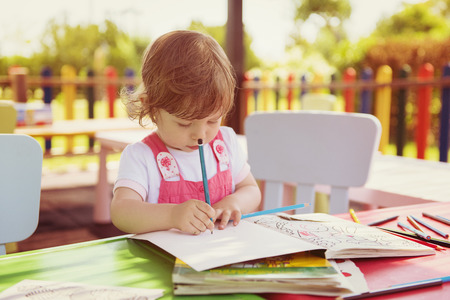 cute little girl cheerfully spending time using pencil crayons while drawing a colorful pictures in the outside playschool 版權商用圖片