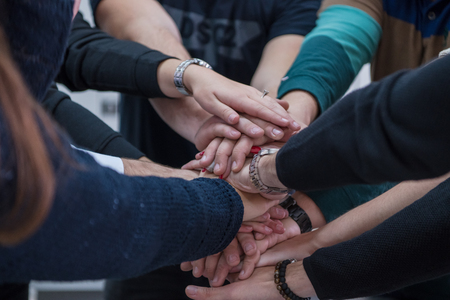 Group of young students in electronics classroom celebrating successfully finished project with holding their hands together, education and technology concept