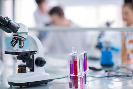 Microscope on the workplace near test tubes with different liquid. Healthcare and biotechnology concept