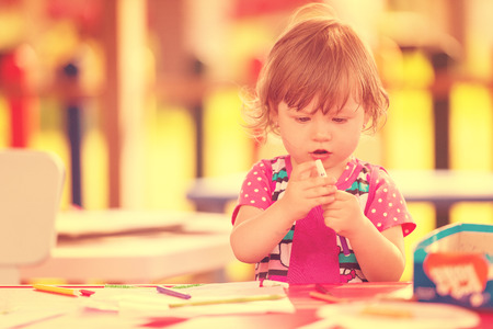 cute little girl cheerfully spending time using pencil crayons while drawing a colorful pictures in the outside playschool Standard-Bild