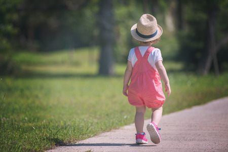 cute little girl with hat cheerfully spending time while running at Park on the summer morning