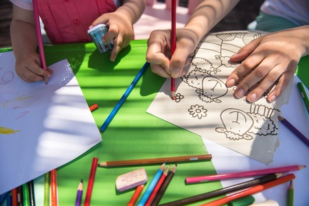 young mother and her little daughter cheerfully spending time together using pencil crayons while drawing a colorful pictures in the outside playschool