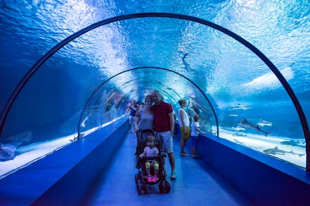 happy young family with little daughter in baby stroller cheerfully spending time in the underwater aquarium