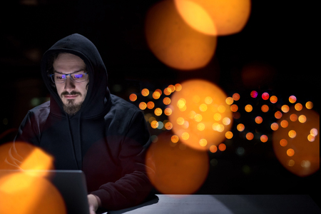 Young talented hacker using laptop computer while working in dark office with big city lights in the  night