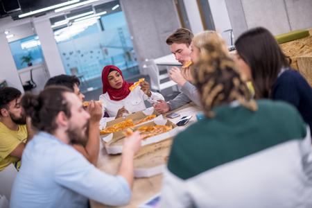 友好多元的多民族商务团队在创业办公室一起吃披萨,多民族的同事们享受着休息时间,在会议的午餐时间谈笑
