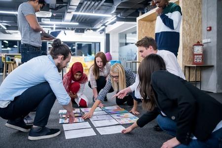 młoda czarna muzułmańska bizneswoman spotyka się ze swoim wieloetnicznym zespołem startupowym w nowoczesnym wnętrzu biurowym, prezentując nowe pomysły na podłodze