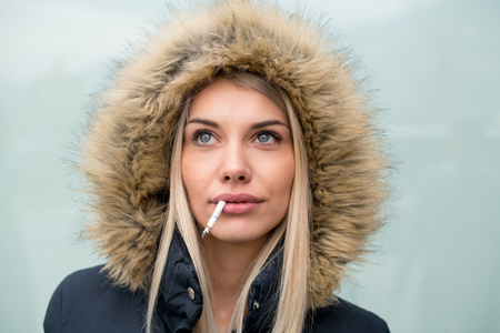 portrait of young blonde girl wearing winter jacket with a hood and cigarette in the mouth isolated over white background Stok Fotoğraf