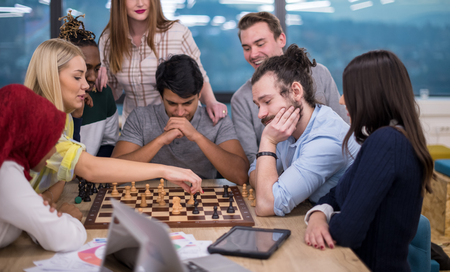 a multiethnic group of business people playing chess while having a break in modern startup office
