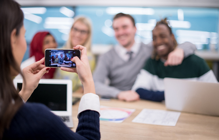businesswoman using mobile phone for taking photo of her multiethnic business team at modern startup office