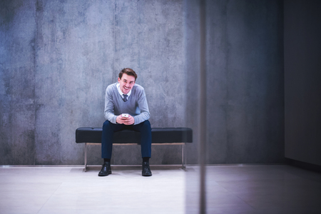 young businessman using smart phone while sitting on the bench at office lobby during a break