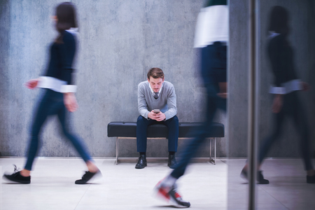 young businessman using smart phone while sitting on the bench at busy office lobby during a break