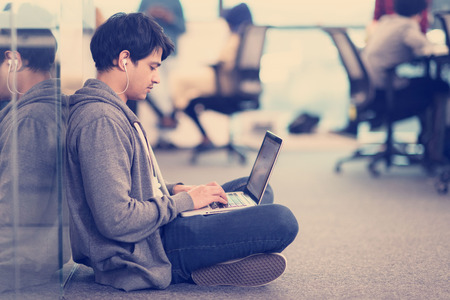 Young indian software developer man using laptop computer writing programming code while sitting on the floor at modern creative startup office Banco de Imagens