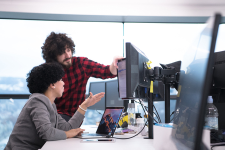 Young software developers couple using laptop and desktop computer while writing programming code at modern creative startup office