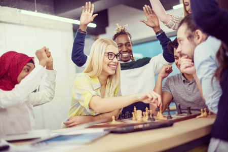 A multiethnic group of business people playing chess while having a break in modern startup office Stock Photo