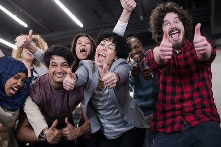 Portrait of young excited multiethnics business team of software developers standing and looking at camera while celebrating success at modern startup office