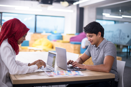 Young  muslim business woman having a meeting with her indian male colleague working on the laptop at modern startup office