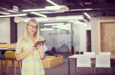 Young blonde businesswoman working online using digital tablet while standing at modern startup office with multiethnic business team