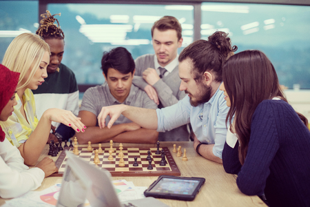Young multiethnic group of business people playing chess while having a break in modern startup office