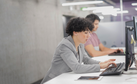 Young female software developer using desktop computer while writing programming code at modern creative startup office Stock Photo