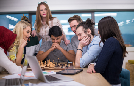 A multiethnic group of business people playing chess while having a break in modern startup office Imagens
