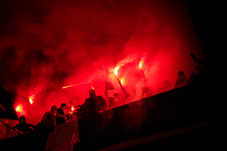 football hooligans with mask holding torches in fire while supporting their favorite team during a match at stadium Editorial