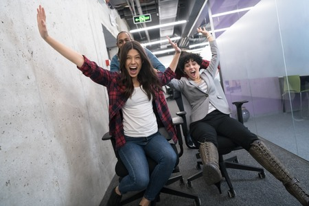 multiethnics startup business team of software developers having fun while racing on office chairs,excited diverse employees laughing enjoying funny activity at work break, creative friendly workers playing game together