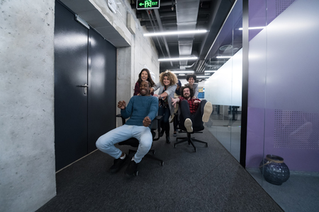 multiethnics startup business team of software developers having fun while racing on office chairs,excited diverse employees laughing enjoying funny activity at work break, creative friendly workers p