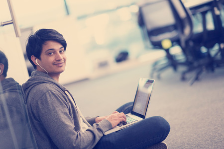 young indian software developer man using laptop computer writing programming code while sitting on the floor at modern creative startup office