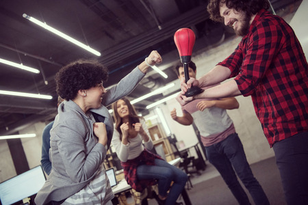 multiethnics startup business team of software developers having fun while boxing at office,excited diverse employees laughing enjoying funny activity at work break, creative friendly workers playing game together Imagens