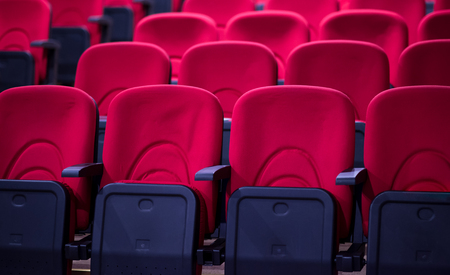 empty conference,theater or cinema hall with rows of red seats Stock Photo