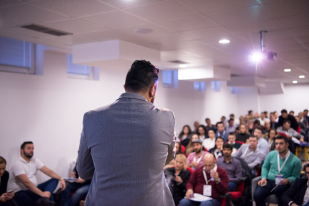 rear view of young successful businessman at business conference room with public giving presentations. Audience at the conference hall. Entrepreneurship club Imagens