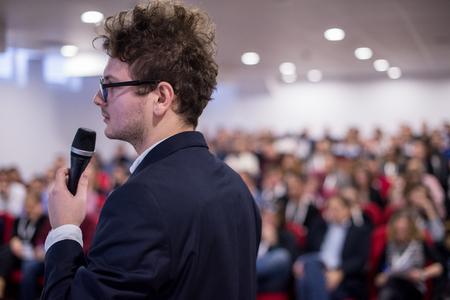 joven empresario de éxito en la sala de conferencias de negocios con presentaciones públicas. Audiencia en la sala de conferencias. Club de emprendimiento