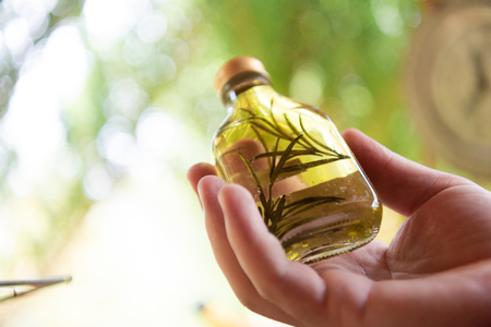Tincture or potion bottle in hand of herbalist  bunch of dry healthy herbs in  alternative medicine
