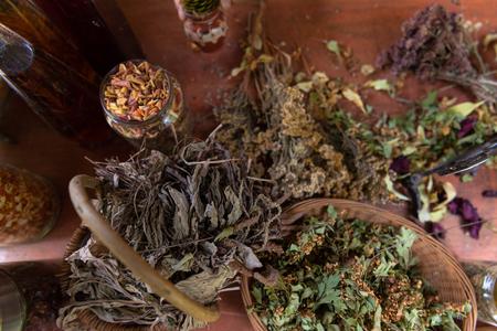 Herbalist workshop with bottles and healing herbs top view