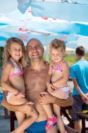 Retrato de joven padre feliz divirtiéndose con sus lindas hijas mientras las sostiene en sus manos junto al mar durante las vacaciones de verano Concepto de vacaciones familiares saludables