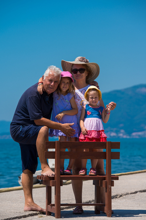 Portrait of  happy grandparents with cute little granddaughters having fun on a bench by the sea during Summer vacation  Healthy family holiday concept