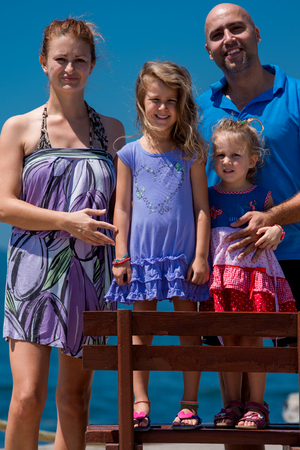 Portrait of young happy family with cute little daughters having fun on a bench by the sea during Summer vacation  Healthy family holiday concept