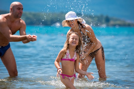 Young happy couple with cute little daughters having fun while splashing each other in the shallow water of the sea during Summer vacation Healthy family holiday concept