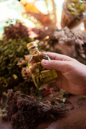 Tincture or potion bottle in hand of herbalist  bunch of dry healthy herbs Stock Photo