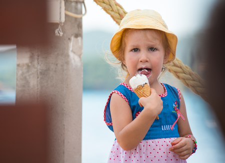 adorable little girl eating ice cream on beach by the sea during Summer vacation Imagens