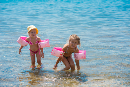 two happy little girls with swimming armbands playing in shallow water of the sea during Summer vacation Healthy childhood lifestyle concept