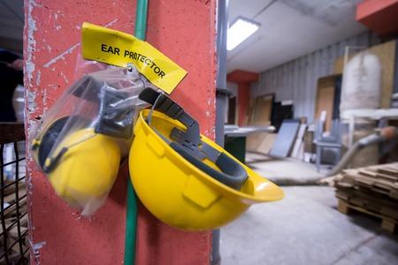equipaggiamento di sicurezza standard casco giallo e protezione per le orecchie appesi al muro nel reparto di produzione di una grande fabbrica di mobili in legno moderno Archivio Fotografico