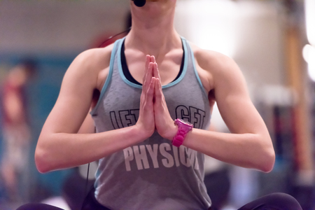 Relaxed young sportswoman doing yoga exercise and meditating in a fitness studio