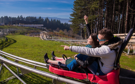 Excited young couple driving alpine coaster while enjoying beautiful sunny day in the nature
