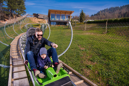 Excited young father and son driving on alpine coaster while enjoying beautiful sunny day in the nature