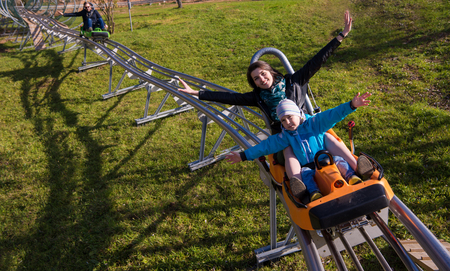 Excited young mother and son driving on alpine coaster while enjoying beautiful sunny day in the nature