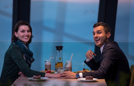 Young happy loving couple enjoying romantic dinner while celebrating Valentines day near the window at luxury restaurant