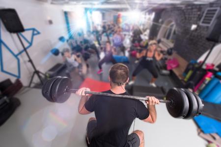 Eine Gruppe junger, gesunder, sportlicher Frauen, die mit einem Trainer mit Langhanteln trainieren, während sie in einem Fitness-, Sport-, Trainings-, Fitness- und Lifestyle-Konzept trainieren Standard-Bild