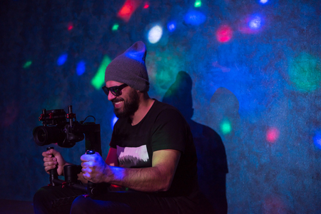 Young videographer with gimball video slr working in kids neon disco party